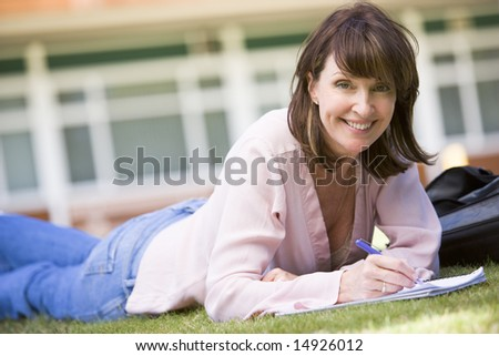 A woman writing notes while lying on a campus lawn - stock photo