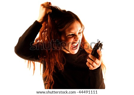 A woman yelling into a phone in front of a white background. - stock photo