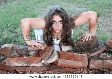 A woman zombie rises toward her victim - stock photo