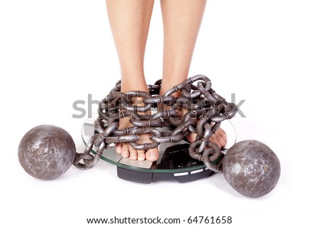 A womans feet are chained to the scales - stock photo