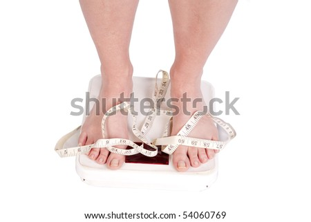 A womans feet on some scales with a tape on them. - stock photo