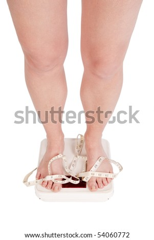 A womans legs and feet on scales with a measuring tape on them. - stock photo