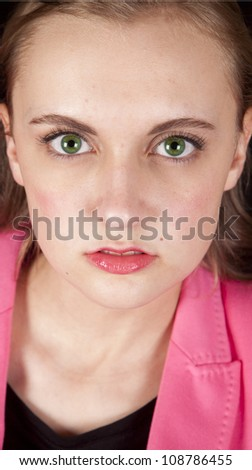 A womans portrait with green eyes and a pink jacket. - stock photo