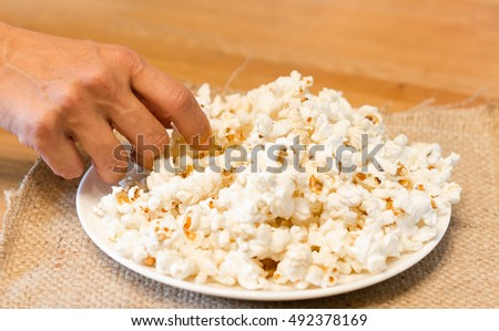 A women hand pick the popcorn on white plate