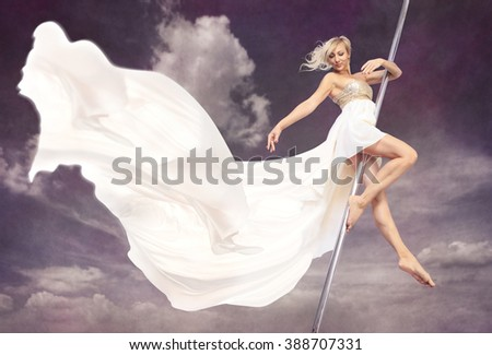 a women in a dress pole dancing in front of sky - stock photo