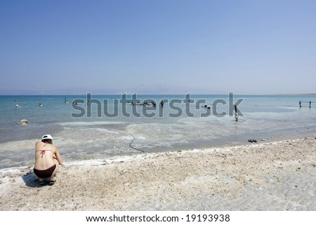 A women pick up salt stones from the Dead Sea beach