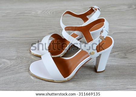 a Women's white sandals  on the floor - stock photo