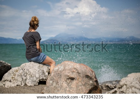 A women sit on the Gardasee and looking in the water. Water splash around from the surf