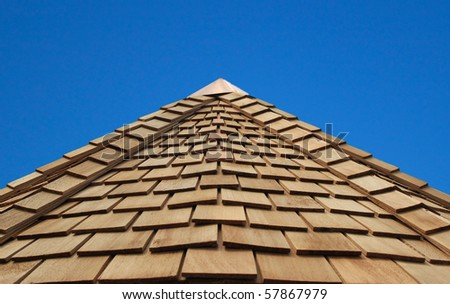a wonderful blue sky behind a cladded wooden roof - stock photo