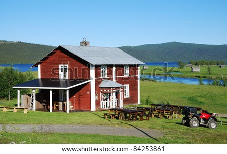 A wood building is on the green meadow. There are a wide lake and the dark hills covering with taiga forest in the background. - stock photo