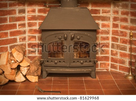 A wood burning stove in a red brick fireplace - stock photo