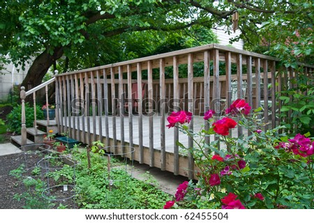 A wood deck nestled under the shade of a huge old tree and surrounded by roses in the back yard.