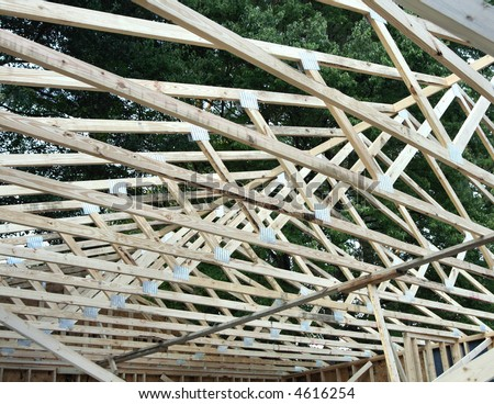 A wood frame roof under construction.  Wood beams and trusses. - stock photo