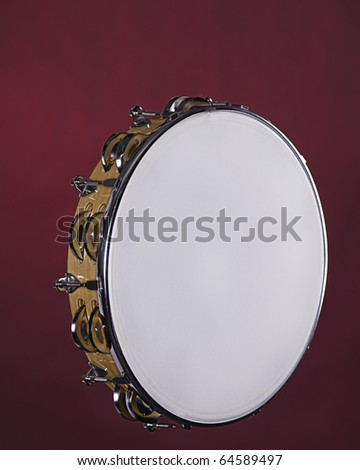 A wood frame tambourine isolated against a red background. - stock photo