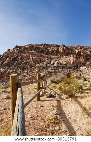 A wood rail fence through the desert towards mountains under blue sky - stock photo