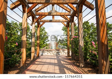 A wood rose trellis over a brick sidewalk toward a fountain in a public garden - stock photo