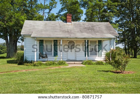 A wood siding house that a realtor would refer to as a fixer-upper. - stock photo