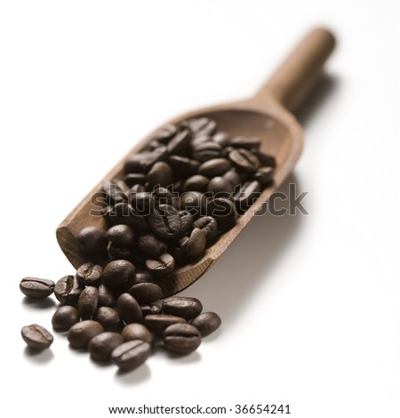 a wood spoon with roasted coffee on white