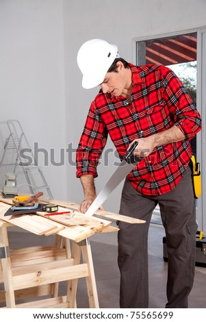 A wood worker using a hand saw in a home interior - stock photo