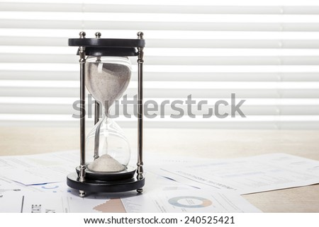 A wood working(office) table(desk) with sand timer(hour glass) on the graph paper(document)s for business behind blind(rolling blind, shade).   - stock photo