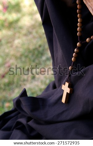 A wooden anglican rosary with a cross is hanging on a black fabric - stock photo