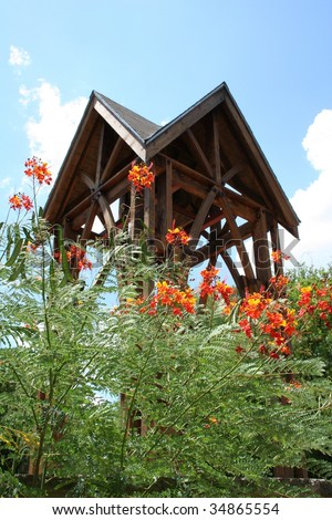 A wooden bell tower and wild flowers - stock photo