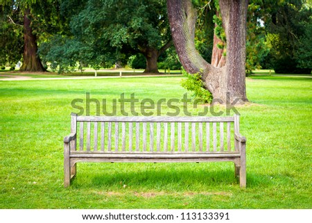A wooden bench in lush green parkland in summer - stock photo