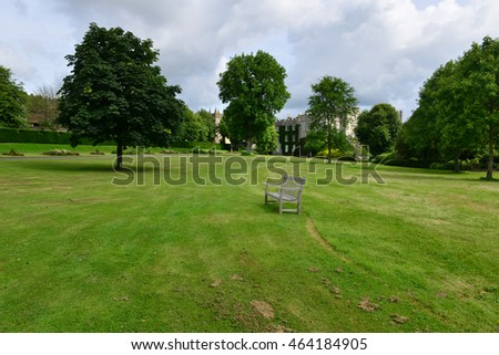 A wooden bench on a manicured lawn in an English country garden in summer.