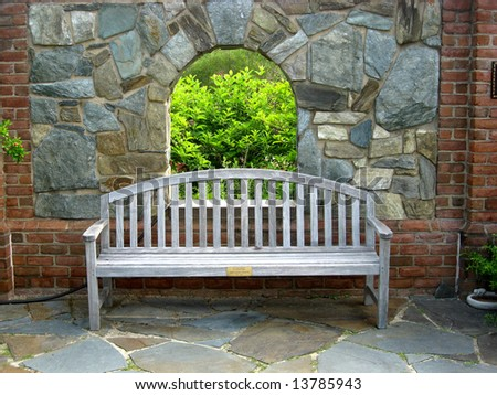 A wooden bench on a patio with stonewall blocking the view into the garden.  A small arch window in the stonewall allows a small view into the garden beyond.