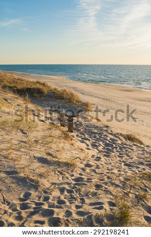 A wooden bench on the beach at sunset - stock photo