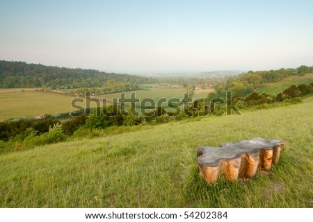A wooden bench shaped like a leaf is in the foreground of a landscape shot of the North Downs in Surrey, UK.