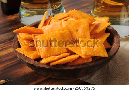 A wooden bowl of cheese flavored crackers and glasses of beer - stock photo