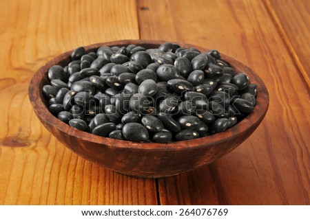 A wooden bowl of dried organic black beans - stock photo
