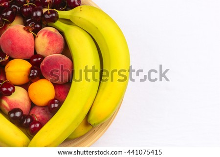 A Wooden Bowl of Fruits on a Wooden Background, Banana, Cherries, Peaches.