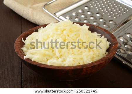 A wooden bowl of grated swiss, mozzarella, or Monterrey Jack cheese - stock photo