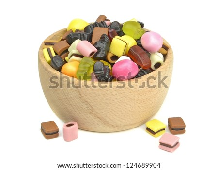 A wooden bowl of mixed sweets on a white background