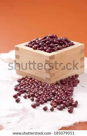 A wooden box had a bunch of beans on top of it and in front. - stock photo