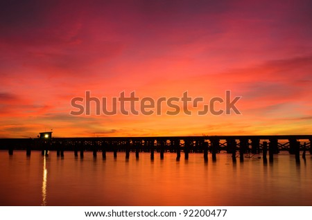 a wooden bridge over a river at sunrise - stock photo