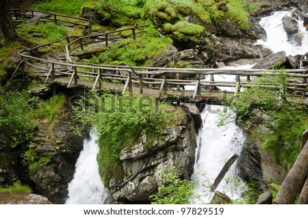 A wooden bridge over the so called Saent waterfalls, formed by the river Rabbies, in the Italian Dolomites - stock photo