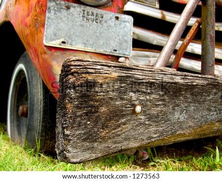 A wooden bumper on a beat up ,old, run down, rusting truck.  Medium DOF, sharp focus on the bumper. - stock photo