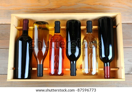 A wooden case of assorted wine bottles without labels on a wood plank winery floor. Horizontal format overhead view. - stock photo