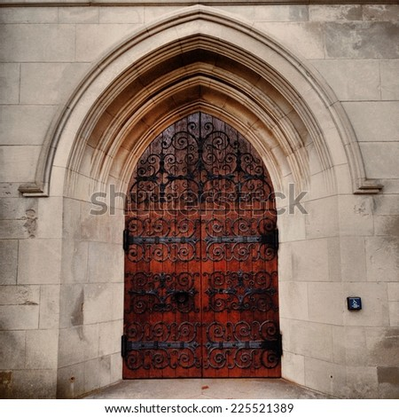A wooden church door framed by a stone arch. - stock photo
