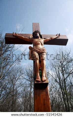 A wooden cross, a crucifix against the blue sky - stock photo