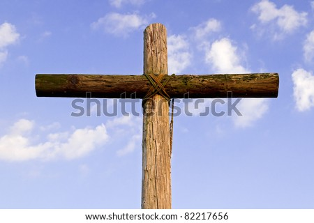 A wooden cross against a blue sky with clouds - stock photo