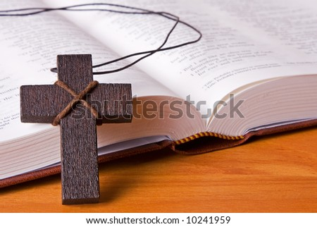 A wooden cross resting against The Holy Bible. Perfect fir use with any religious theme. - stock photo