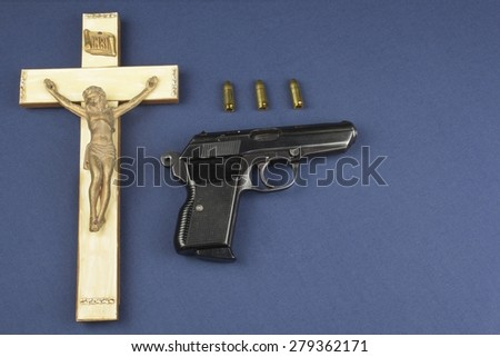 A wooden crucifix with the lettering INRI and gun, Faith and weapon defense of faith - stock photo