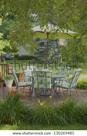 A wooden deck and chairs in spring framed by a tree - stock photo