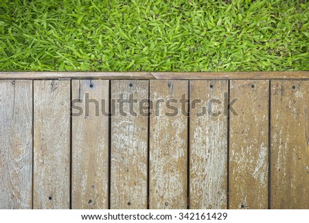 a wooden deck in a garden with view onto the lawn