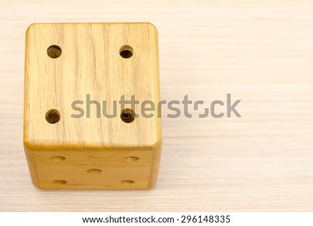 A wooden dice on a wooden table. The number fell to four