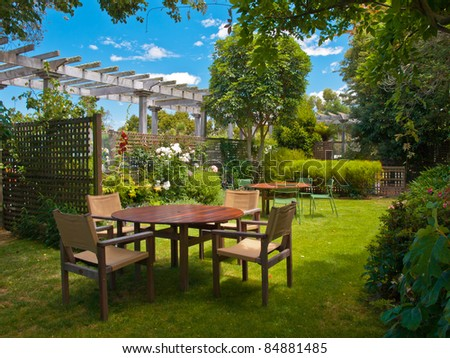 a wooden dining table set in lush garden setting - stock photo